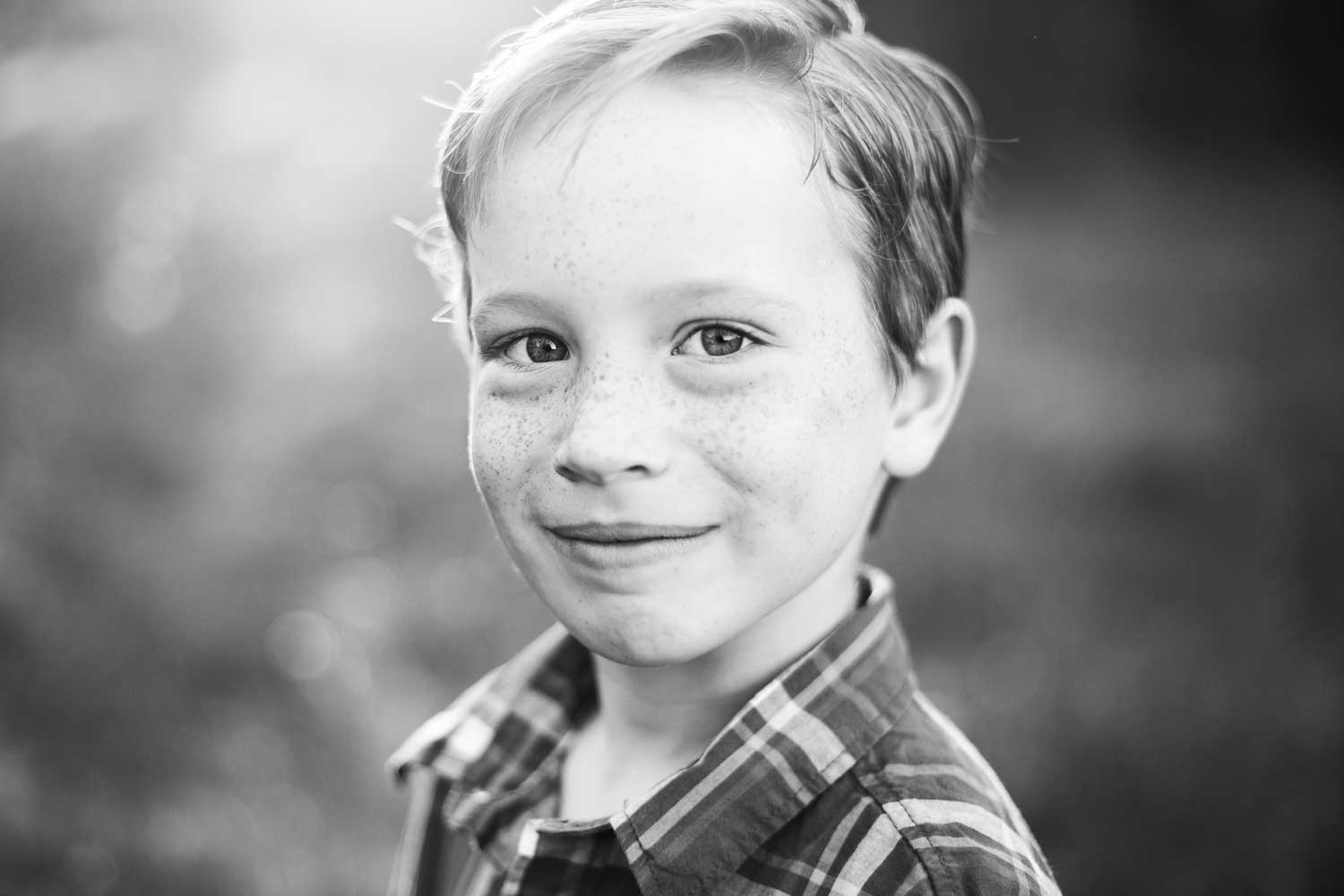 A boy smiles for the camera in Roseville, California during a photo session with Amy Wright Photography.