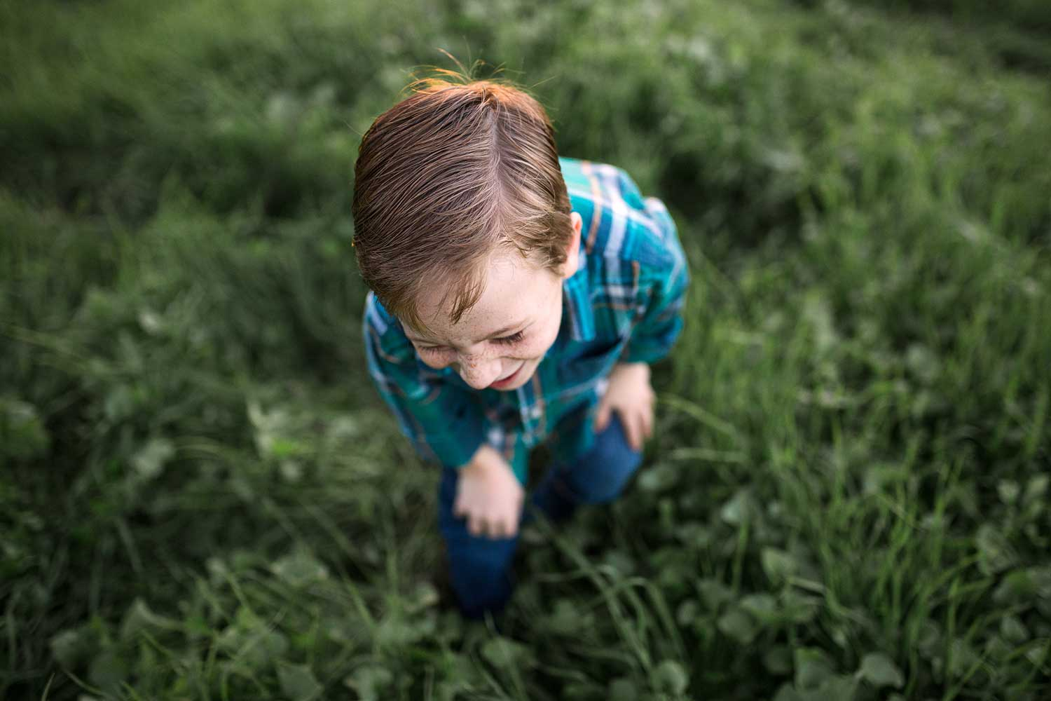 A boy is laughing in a green field in Roseville, California with Amy Wright Photography.