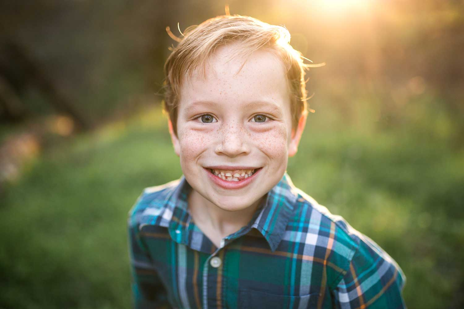 A boy smiles for the camera in some beautiful light in Roseville, California.