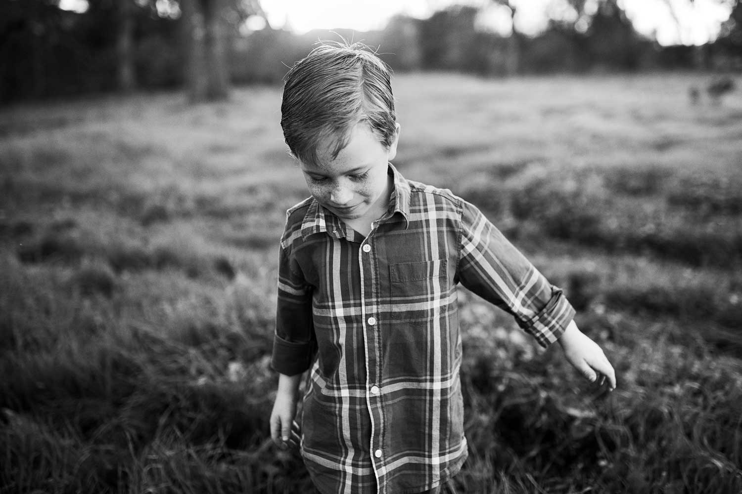 A young boy walks through a grassy field in Roseville, California during a photo session with Amy Wright Photography.