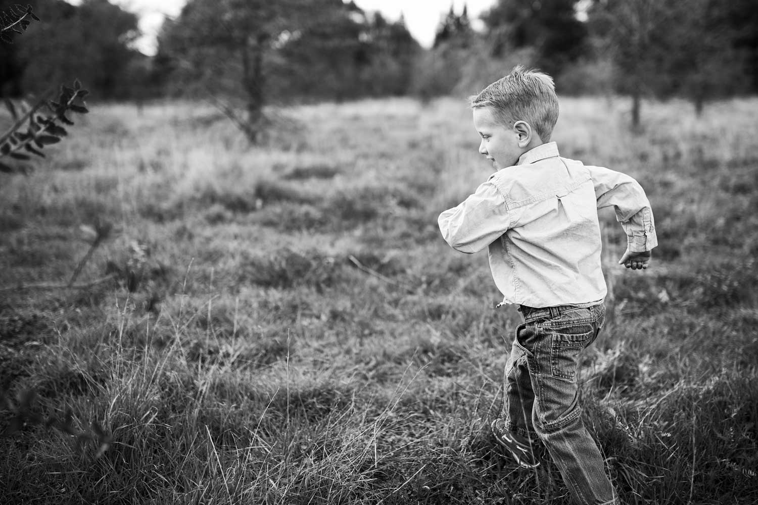 A boy runs in a field in Roseville, California during a photo session with Amy Wright Photography.