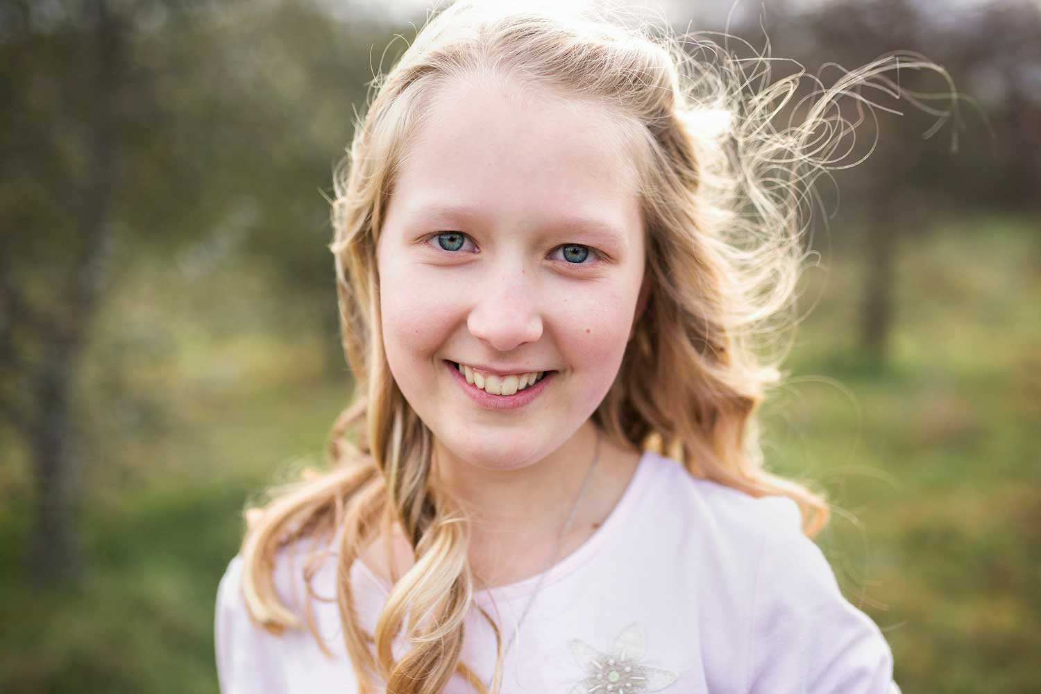 A tween girl looks at the camera and smiles in Sacramento, California with Amy Wright Photography.