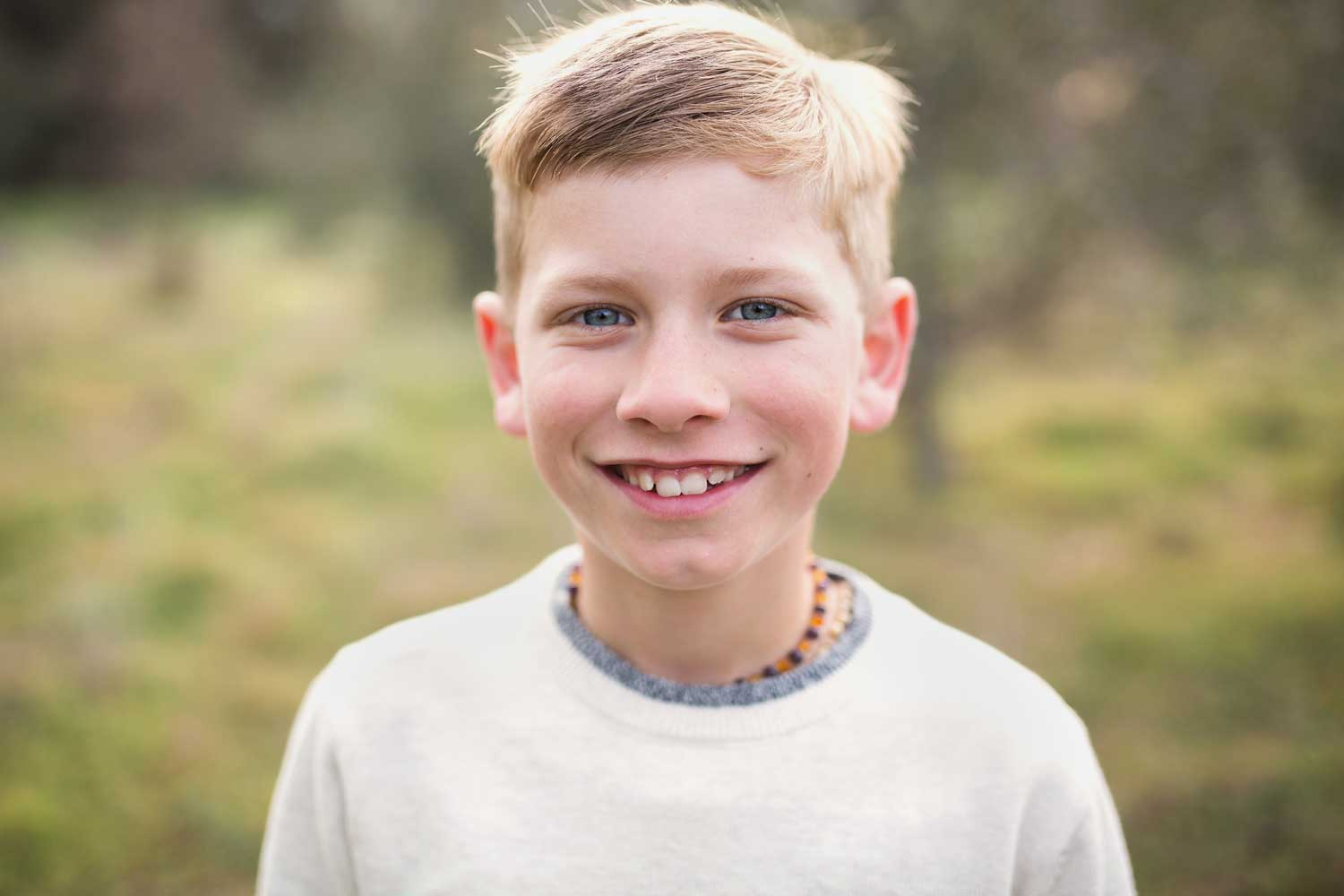 A young boy smiles for the camera during a family photo session with Amy Wright Photography in Sacramento, California.