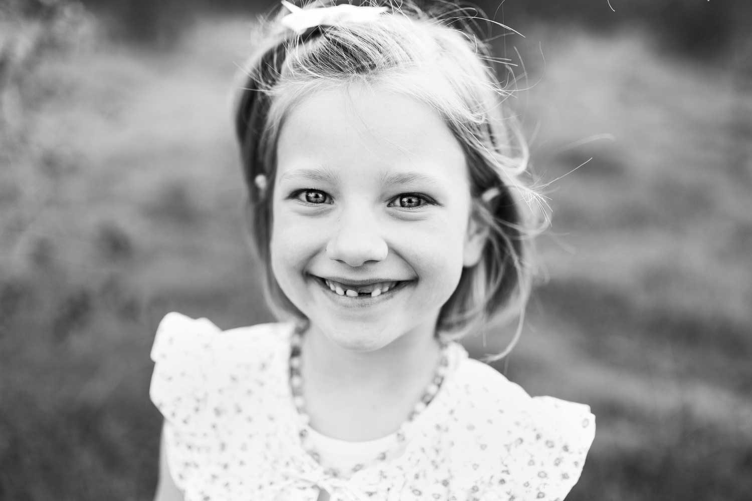 A young girl with missing teeth smiles during a photo session in Sacramento, California with Amy Wright Photography.
