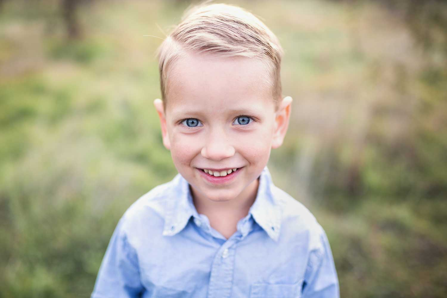 A young boy is smiling for the camera during a photo session with Amy Wright Photography in Roseville, California.