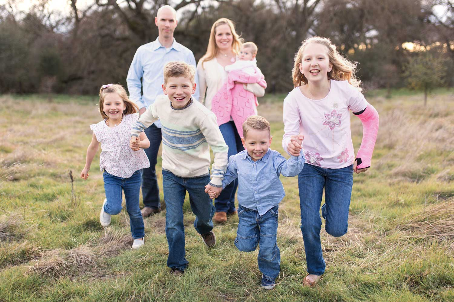 A family of six is running happily through a field in Roseville, California with Amy Wright Photography.