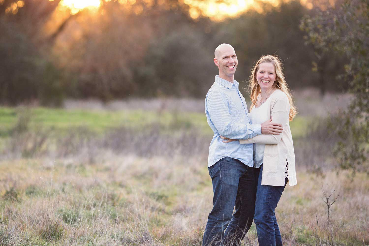 A couple is hugging and laughing together during a family photo session with Amy Wright Photography in Roseville, California.