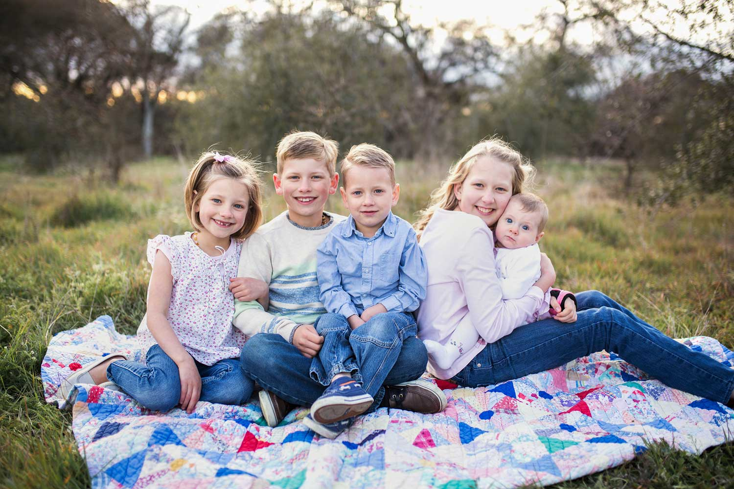 Five siblings sit together and are happy during a photo session with Amy Wright Photography in Roseville, California.