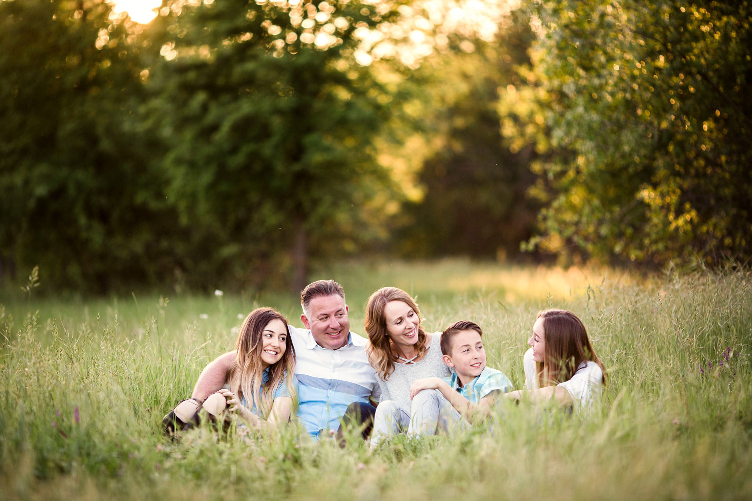 A family of five sits together and enjoys each other's company during a family photo session in Roseville, California.