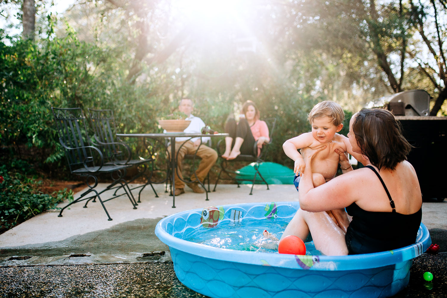 A mother plays and swims with her son during an in-home photo session in Sacramento, California with Amy Wright Photography.