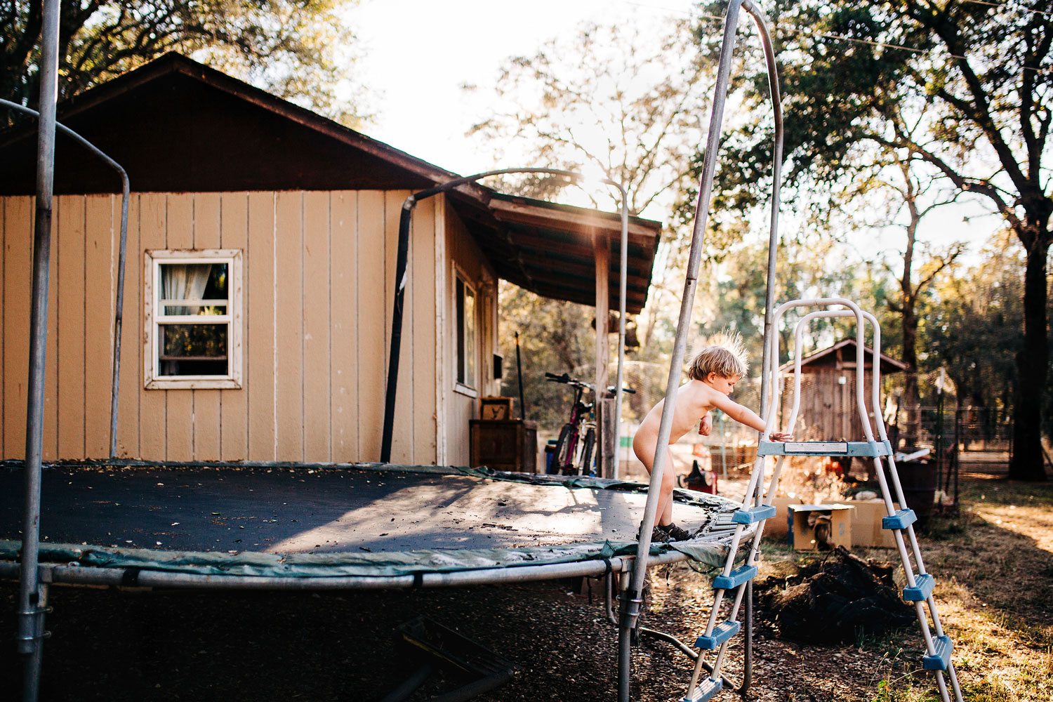 A boy jumps on the trampoline during a lifestyle photo session with Amy Wright Photography in Roseville, California.
