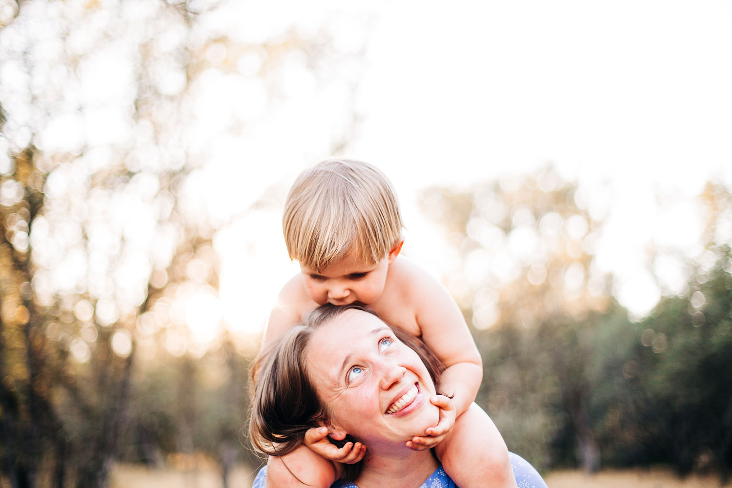 A mother is smiling at her son who has his arms around her and is kissing her. Sacramento, California. Amy Wright Photography.