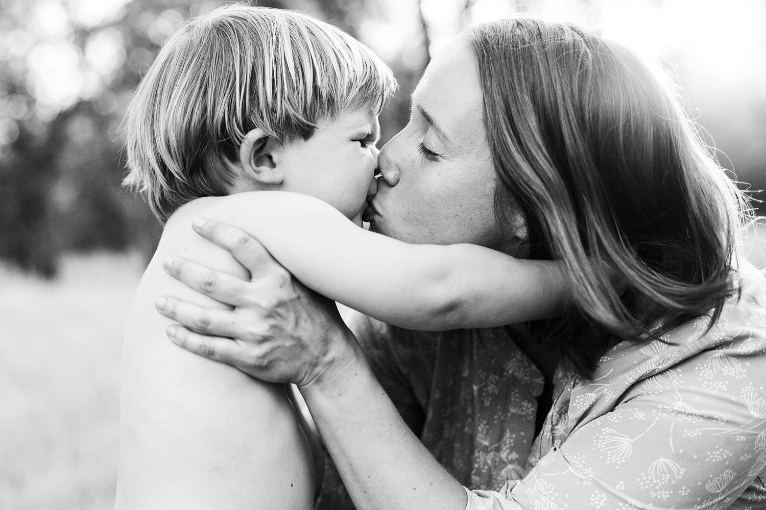 A mother and toddler son kiss during a lifestyle family photo session in Sacramento, California with Amy Wright Photography.