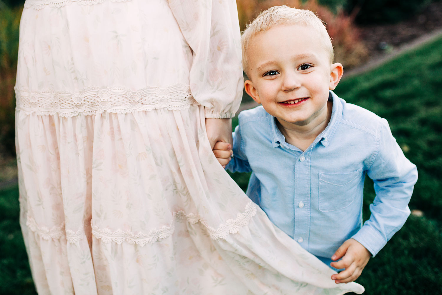 A boy holds his mom's dress during a lifestyle family photo session with Amy Wright Photography based out of Roseville, Rocklin, and Sacramento, California.
