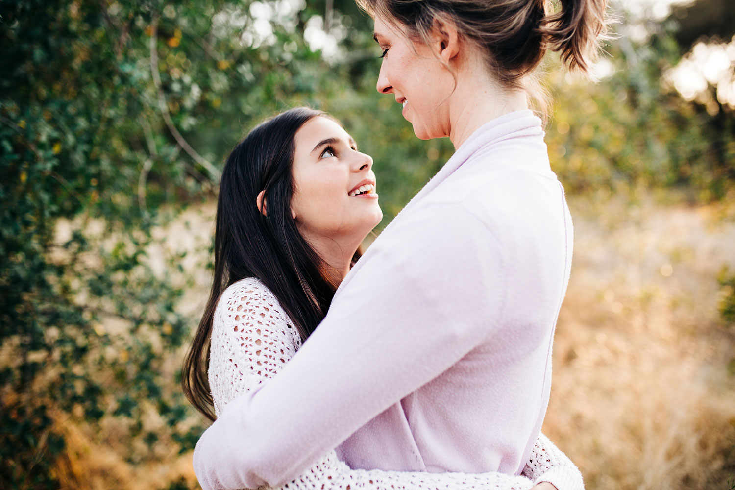 A mother and daughter embrace and look at each other during a photo session with their photographer, Amy Wright, who specializes in lifestyle newborn and family photography in the Sacramento and Roseville, California area.