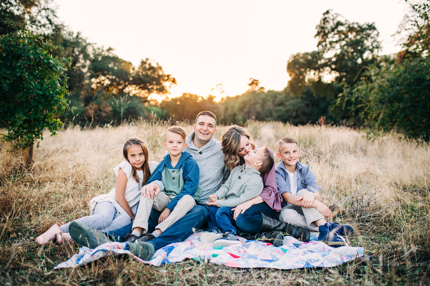 A family of six sits together as the sun goes down for a family lifestyle photo session in Roseville, California with Amy Wright Photography.