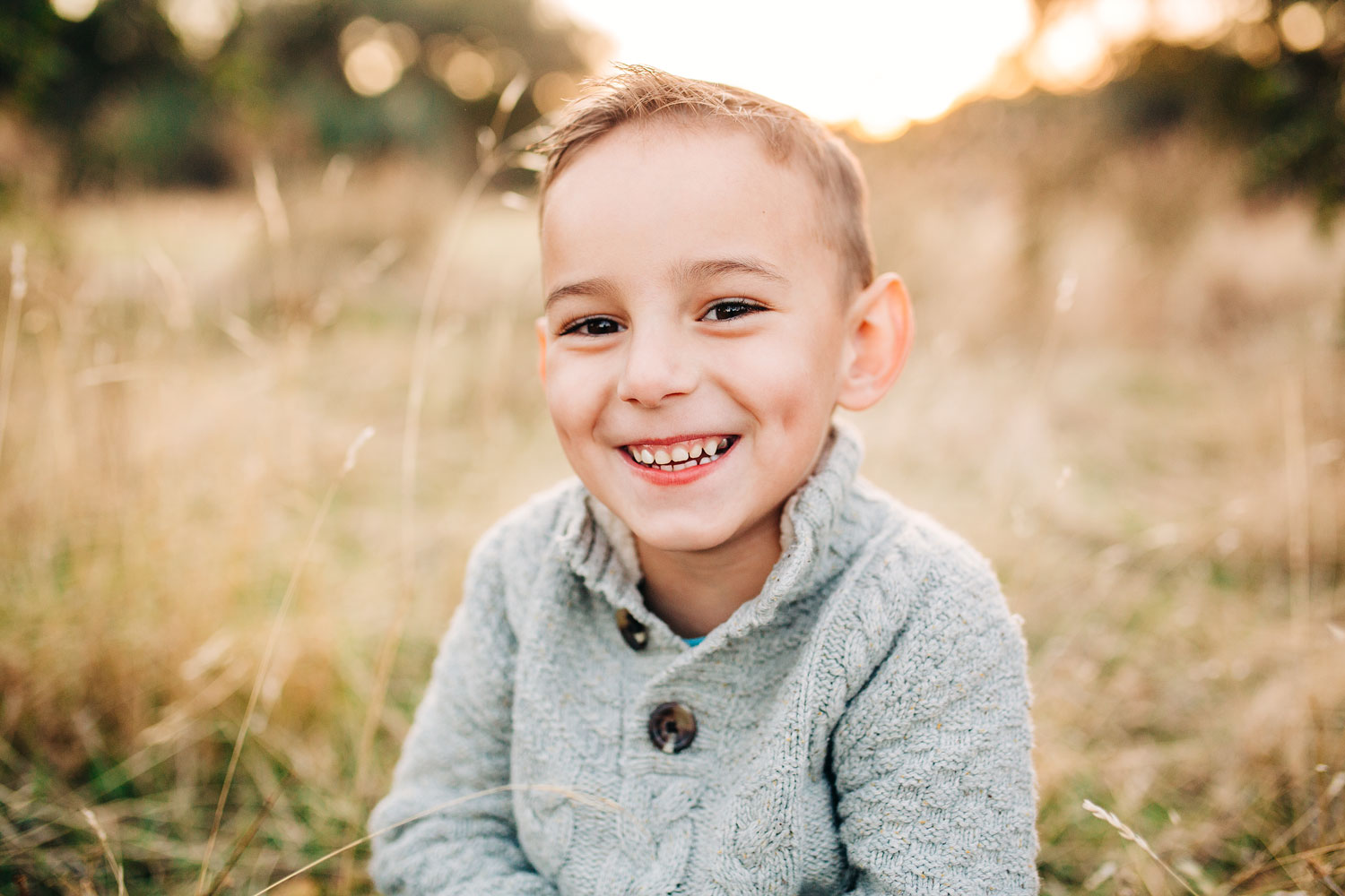 A young boy smiles joyfully during a family photo session with Amy Wright Photography, based out of Roseville, Rocklin, and Sacramento, California.