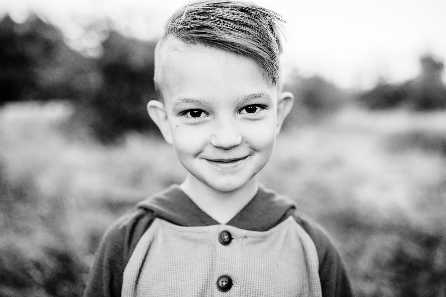 A young boy looks at the camera for his portrait during a lifestyle family photo session with Amy Wright Photography in Roseville, California.