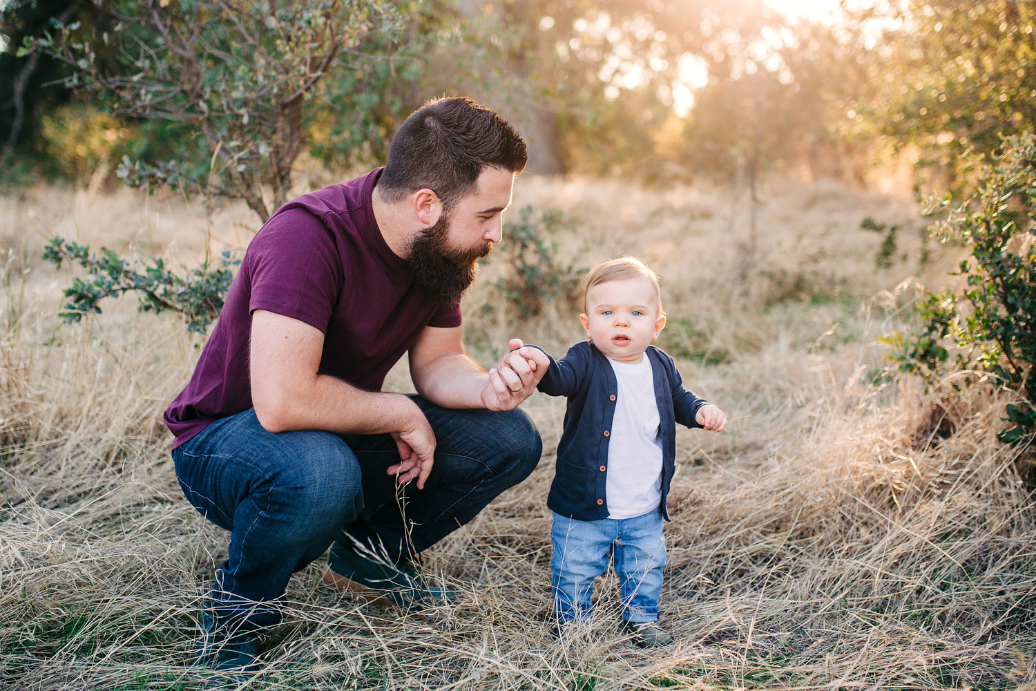 A baby boy stands with the help of his dad during a family mini session with their photography, Amy Wright, based out of Roseville, California.