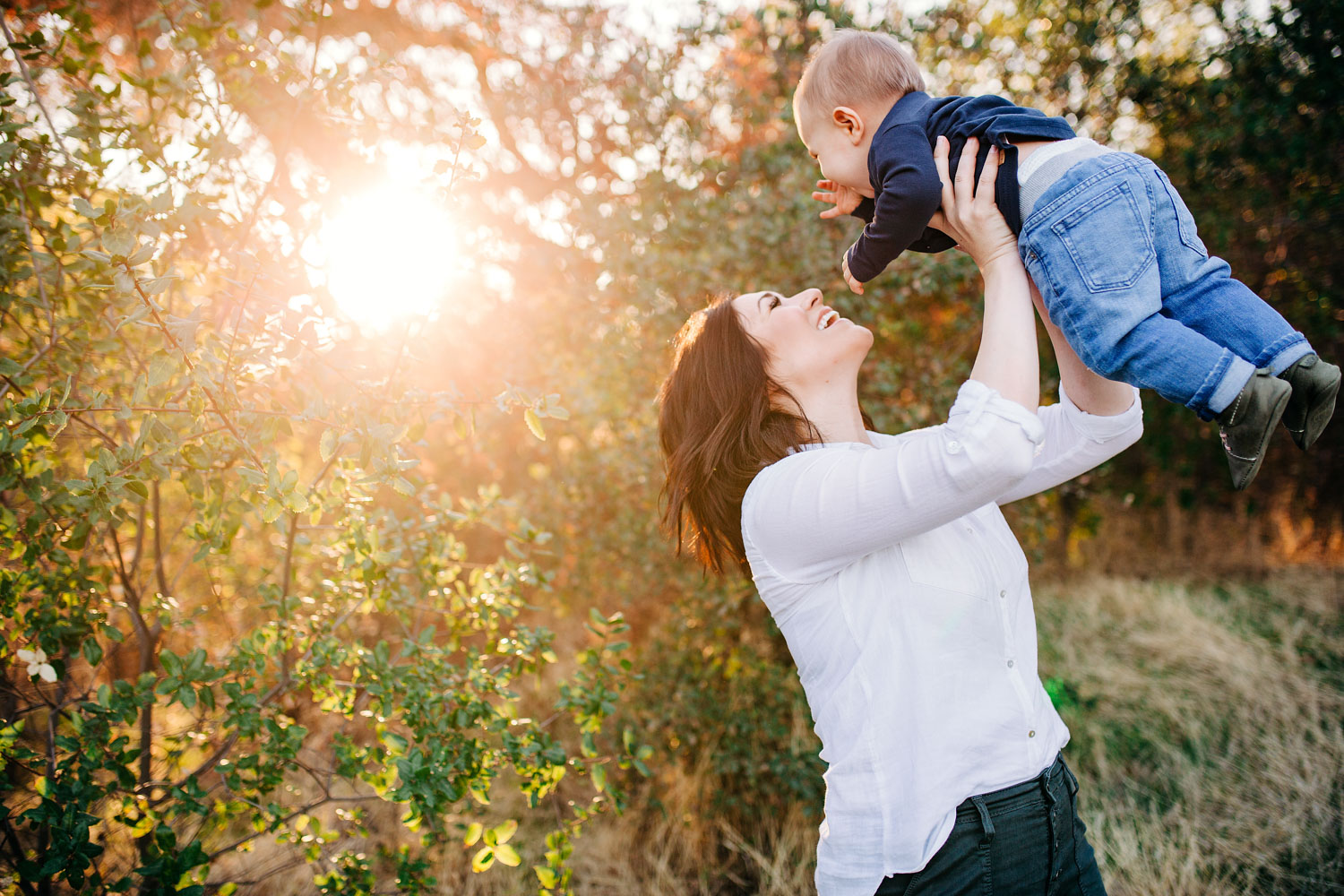 A mother joyfully lifts her baby boy into the air during a fun family photo shoot with Amy Wright Photography in Sacramento, California.