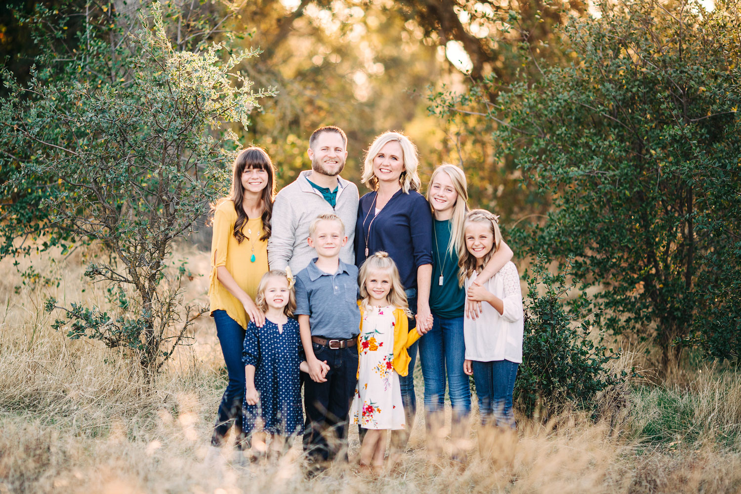A family of eight poses for pictures outside in beautiful light with their photographer, Amy Wright, in Roseville, California.