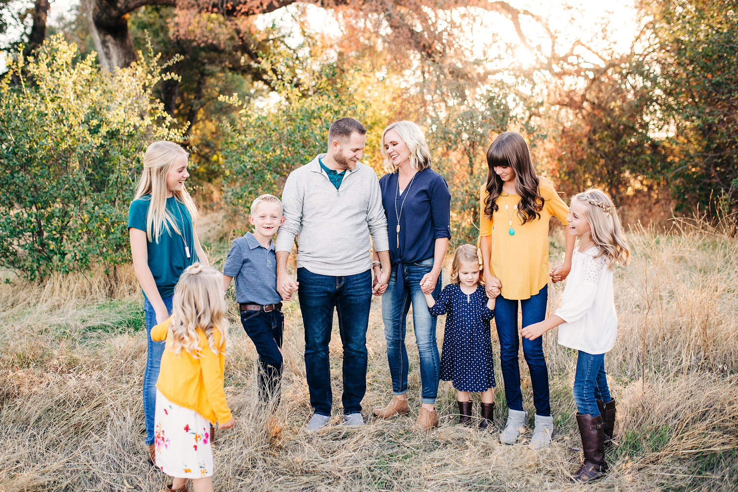 A family laughs together while they hold hands during a lifestyle photo session with Amy Wright Photography in Roseville, California.