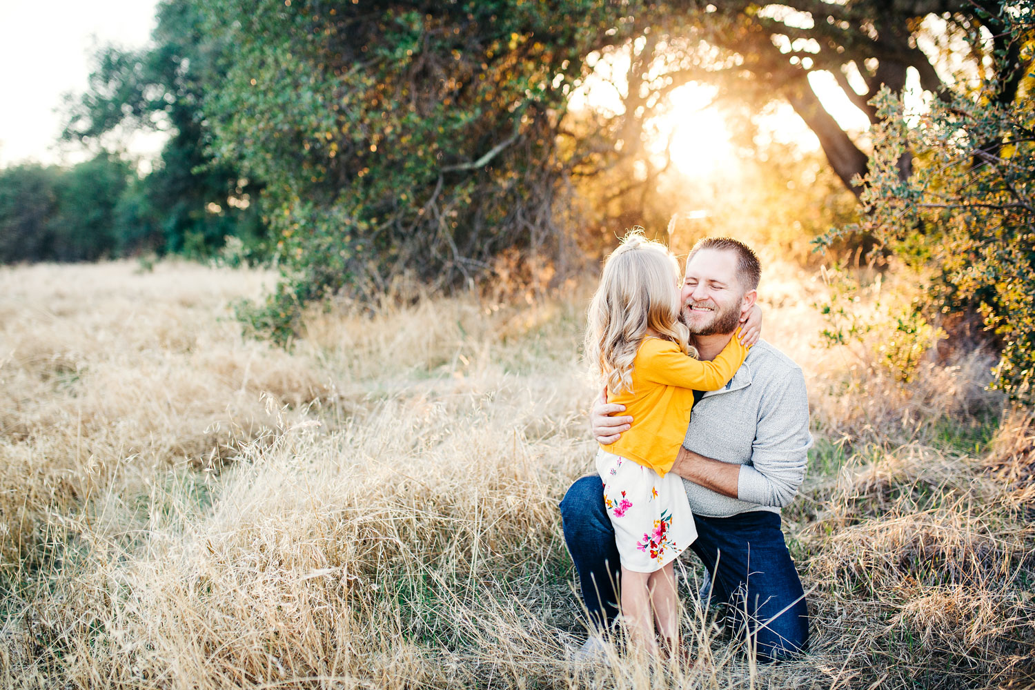 A dad and his daughter hug and have fun together while getting their family pictures taken in Roseville, California by their photographer, Amy Wright.