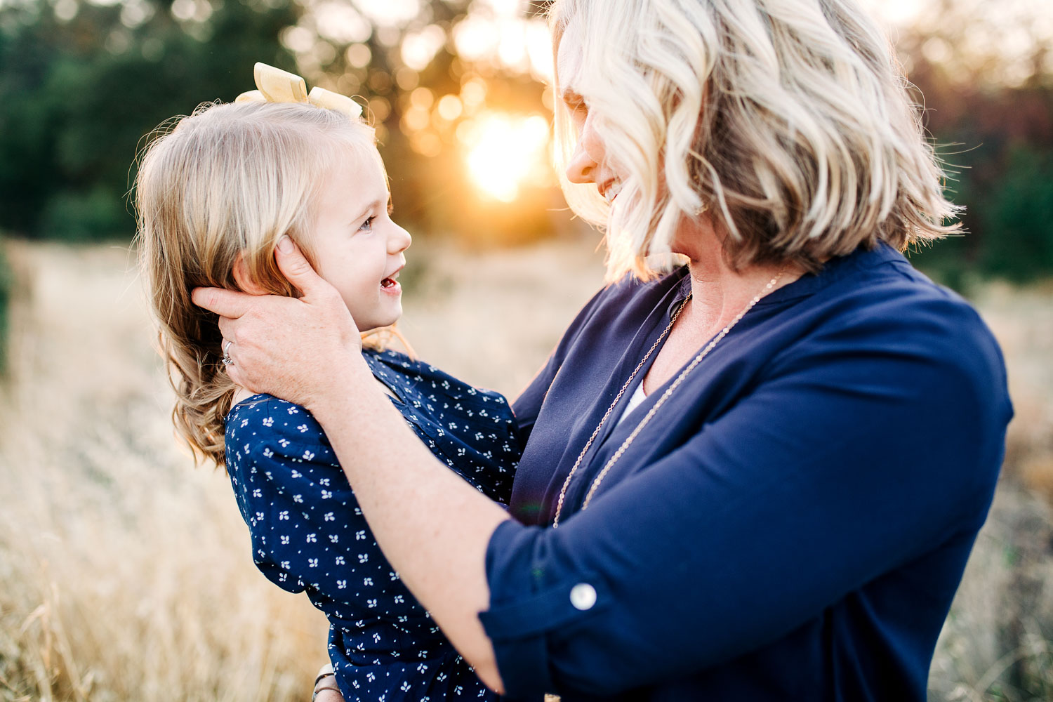 A mom and her daughter look at each other in some beautiful light during golden hour family portraits with Amy Wright Photography in Roseville, California.