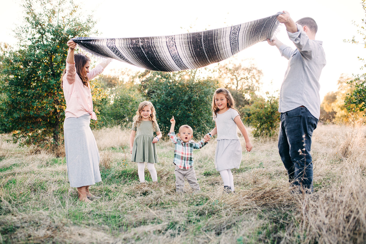 Three children run under a blanket that their parents are holding during a fun filled family photo session with Amy Wright Photography in Roseville, California.