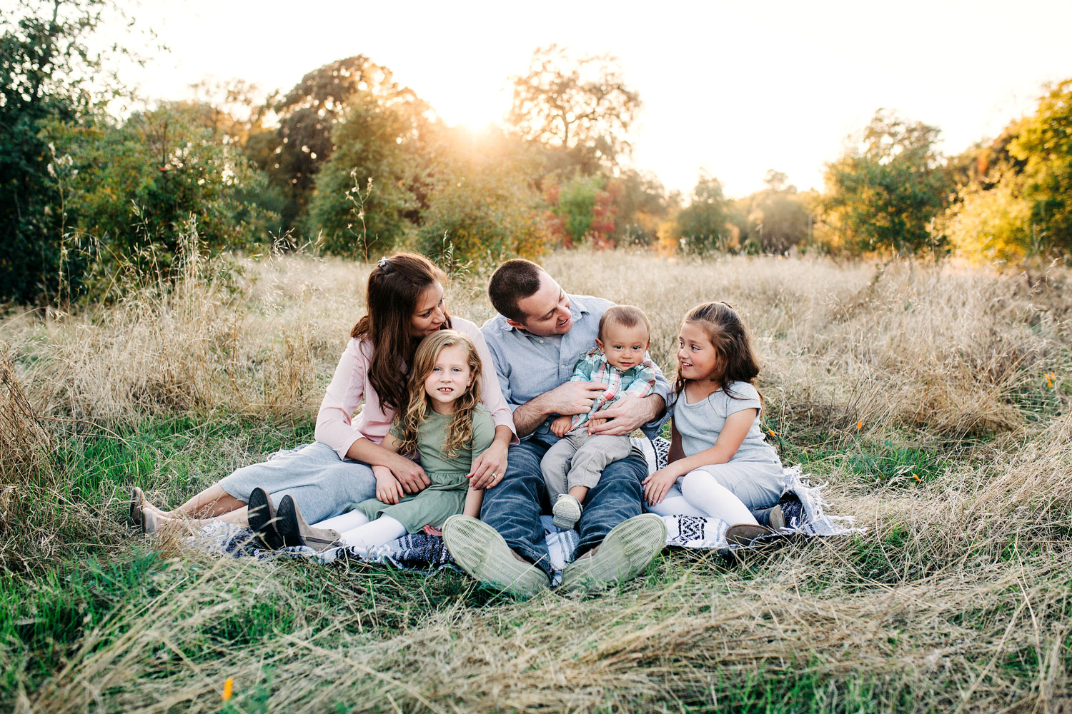 A family of five is sitting together and enjoying each other's company during a lifestyle photo session in Roseville, California with Amy Wright Photography.