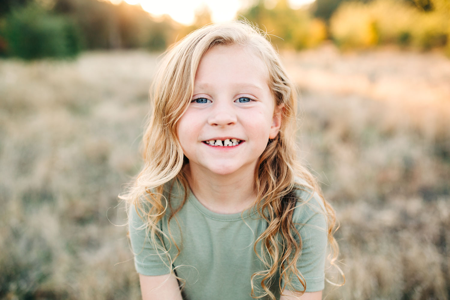 A girl smiles for the camera as she is bathed in beautiful backlit light during golden hour in Roseville, California during her family's photo session with Amy Wright Photography.