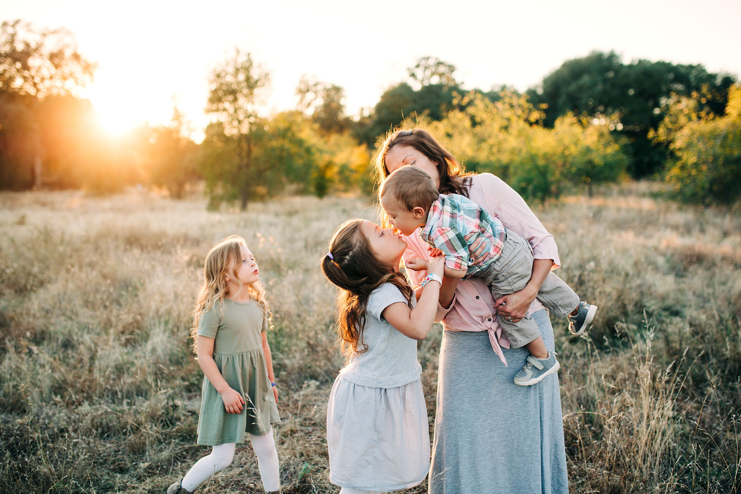 A mother holds her baby while he kisses his big sister during family pictures with Amy Wright Photography in Sacramento, California.