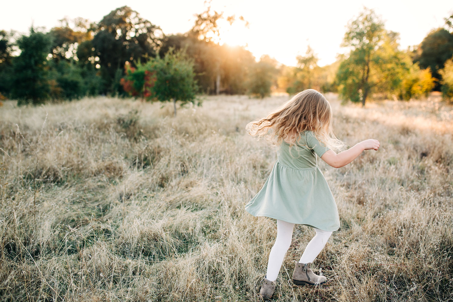 A girl twirls in her dress in the beautiful golden light in Roseville, California during a family photo session with Amy Wright Photography.