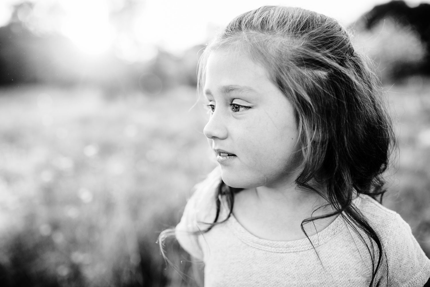 A girl looks to the side in this black and white portrait taken during a family photo session in Sacramento, California by Amy Wright.
