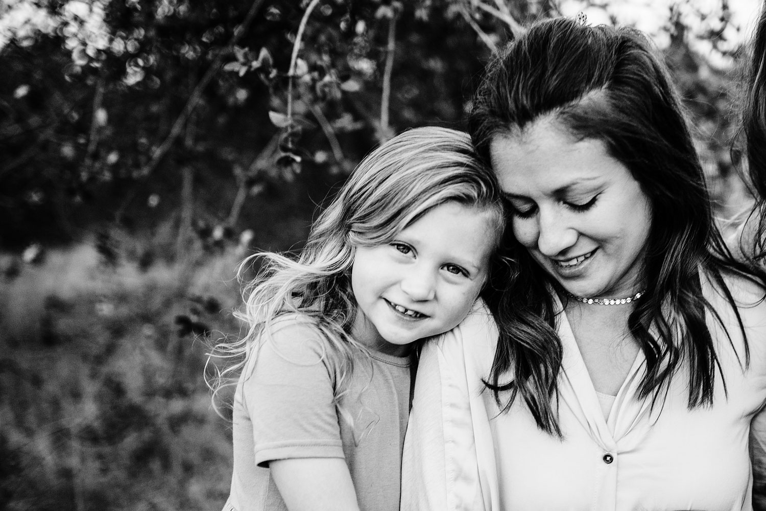 A mother and daughter snuggle together during family pictures with Amy Wright Photography in Roseville, California.