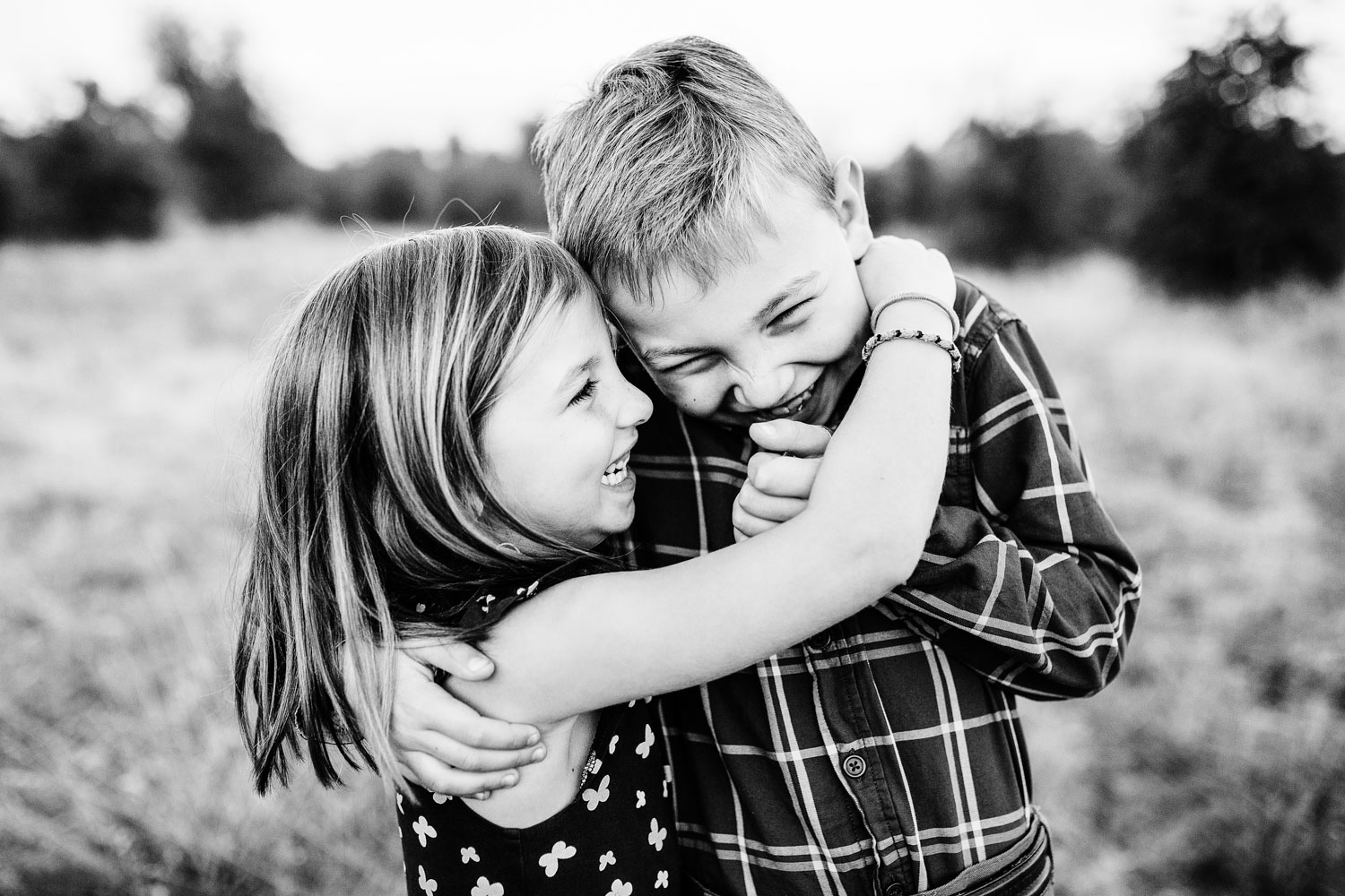 Two siblings put their arms around each other and make one another laugh during family photos with Amy Wright Photography in Sacramento, California.