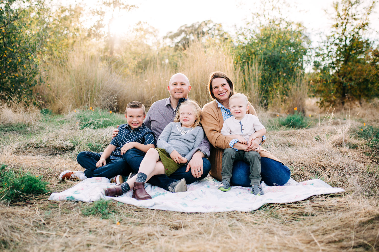 A family of five sit together for pictures with Amy Wright, who is a lifestyle photographer in the sacramento area.
