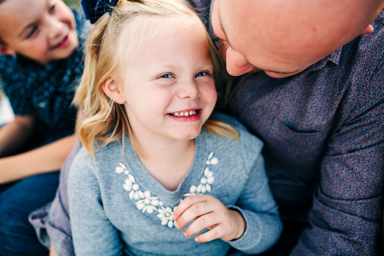 A father snuggles with his happy daughter during a lifestyle family photo session in Roseville, California with Amy Wright Photography.