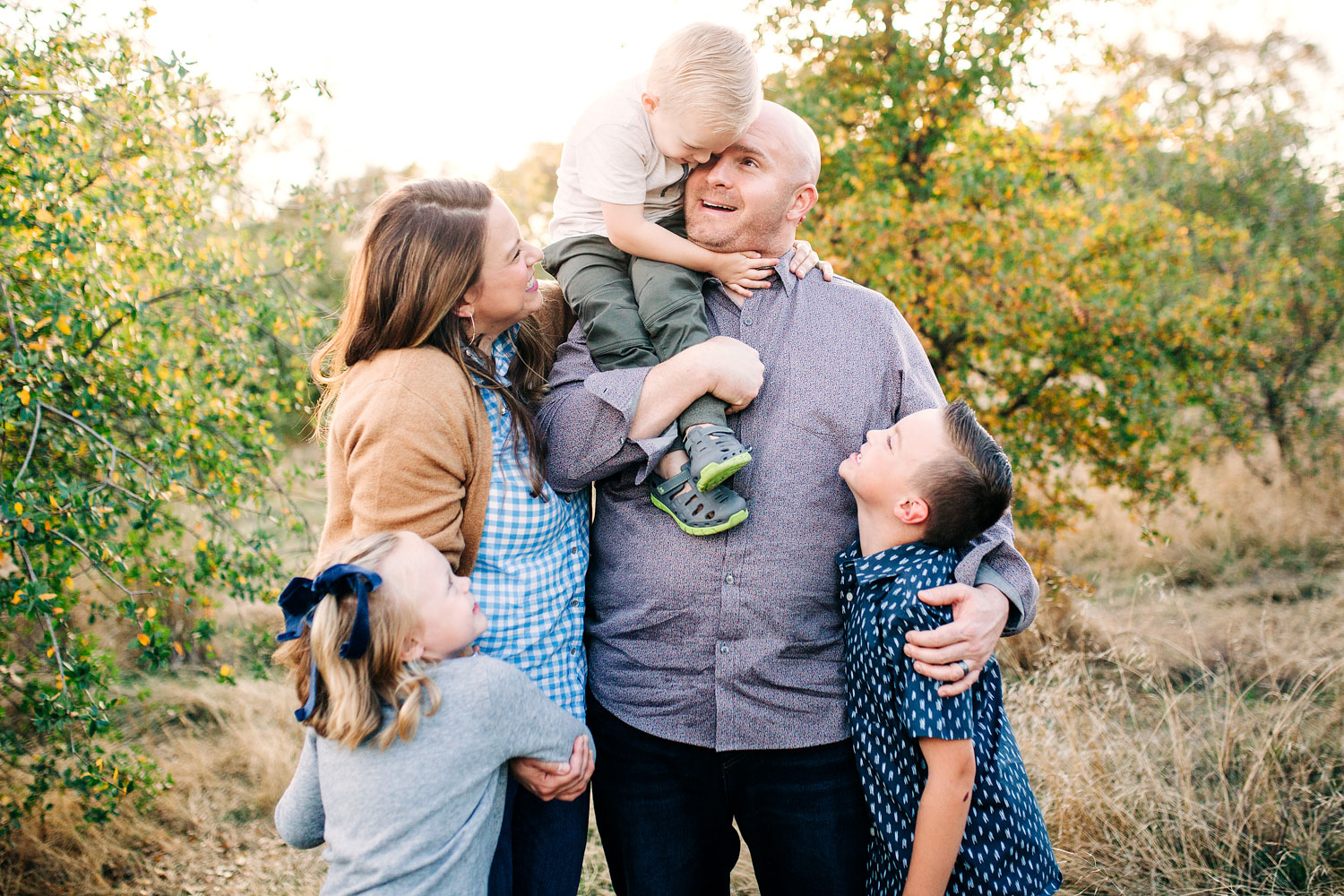 A family of five snuggles and laughs together during a lifestyle photo session with Amy Wright Photography in Sacramento, California.