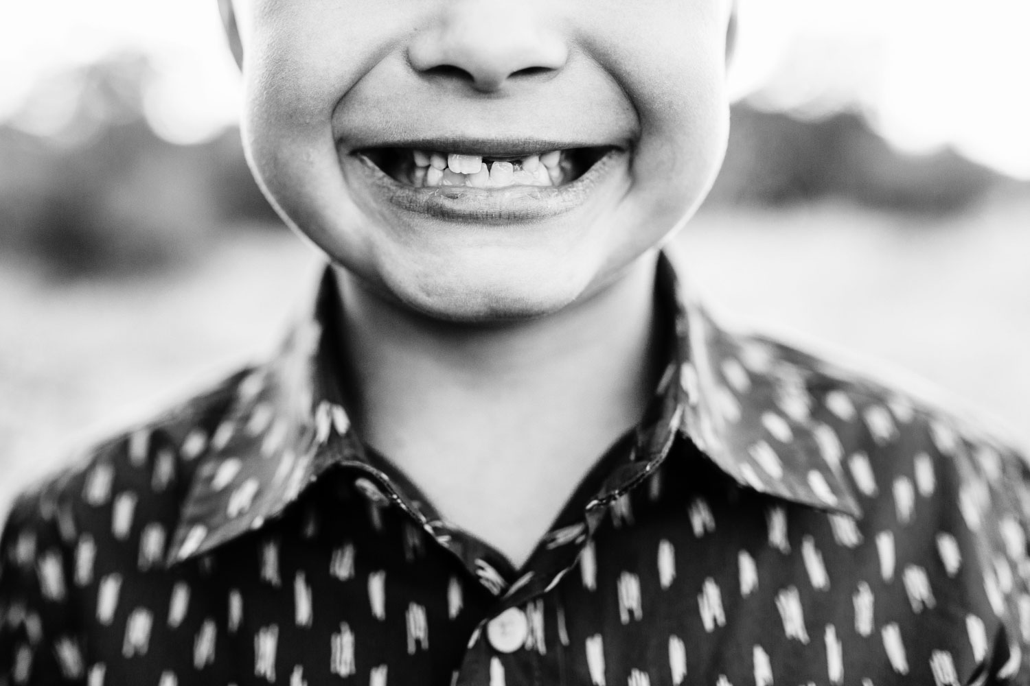 A boy shows off his toothless grin for family pictures with Amy Wright Photography in Roseville, California.