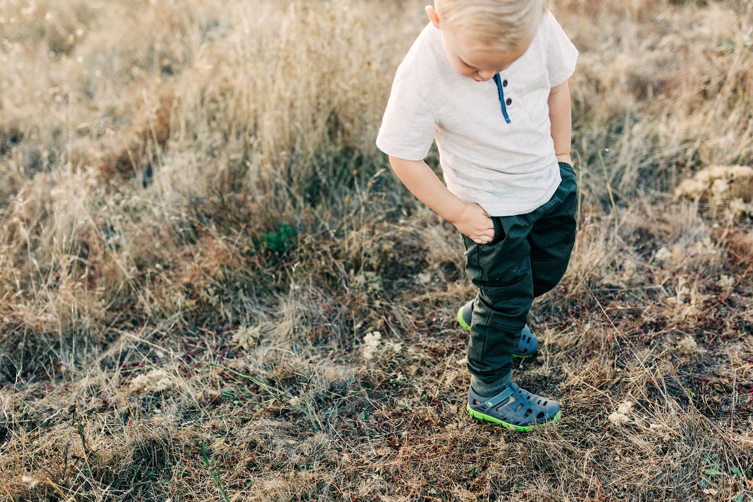 A toddler boy is photographed finding his pockets during a lifestyle family photo session with photographer Amy Wright, based out of Sacramento, California.