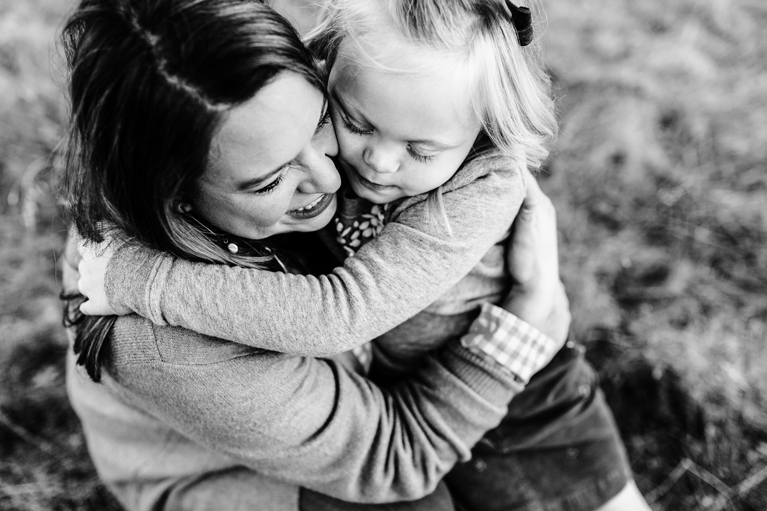 A girl wraps her arms around her mother in love during a lifestyle family photo session with Amy Wright, who is based out of Roseville, California.