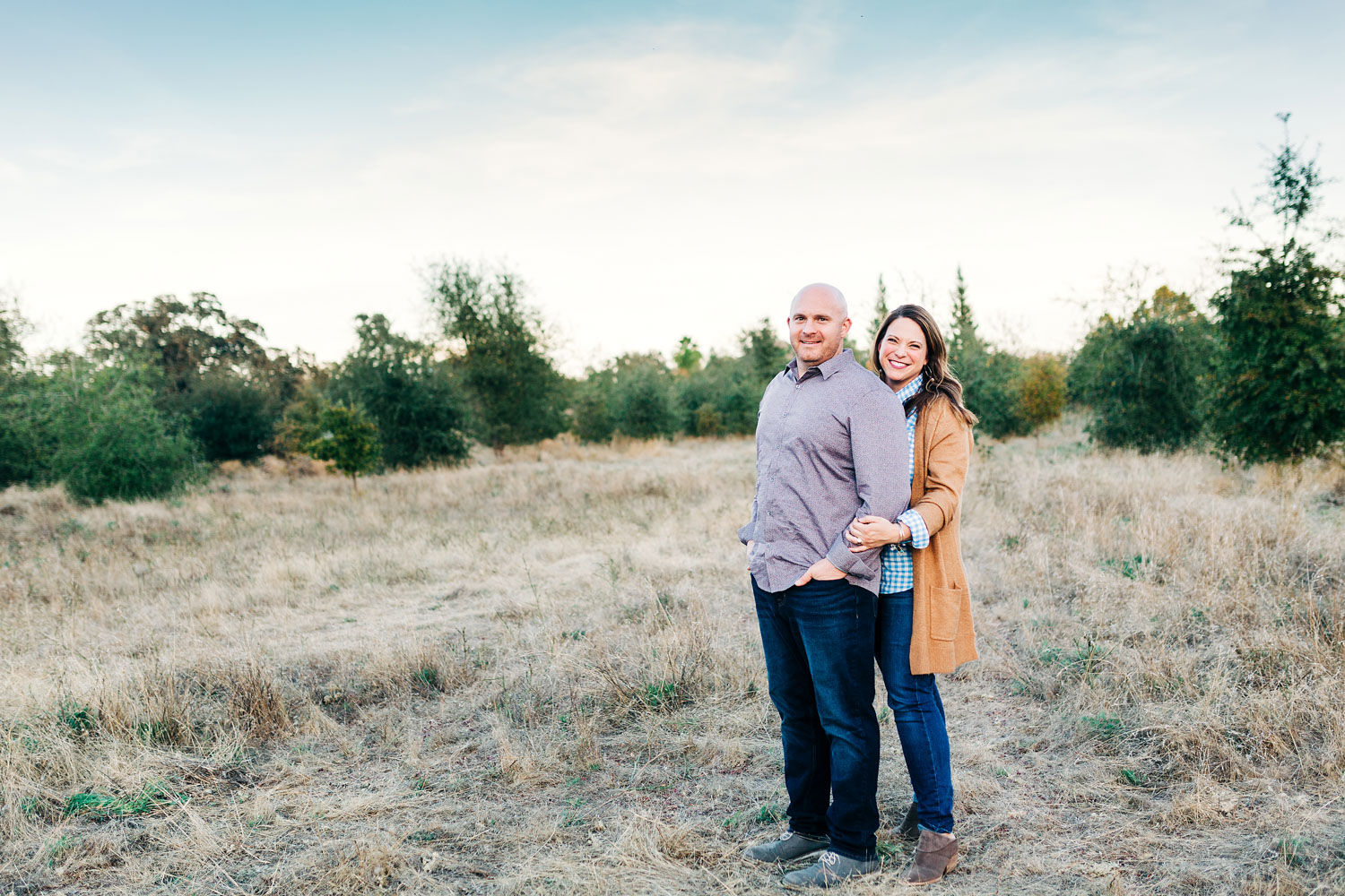 A mom and dad get their photo taken during family pictures in a field in Roseville, California.