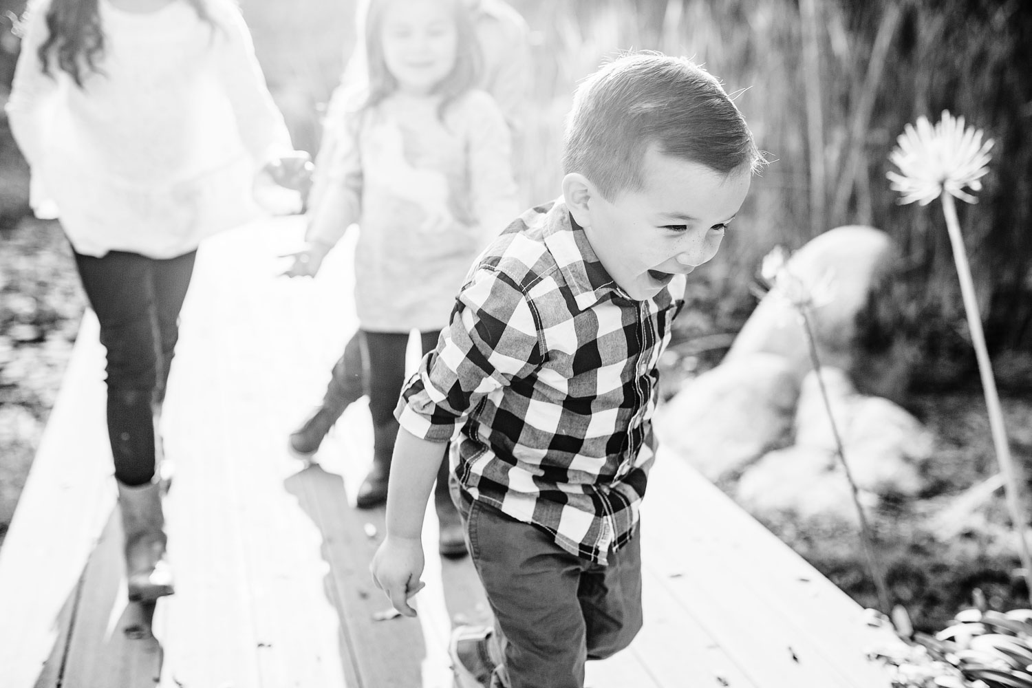 A toddler boy happily runs from his siblings and plays during a family photo shoot with photographer Amy Wright in Sacramento, California.
