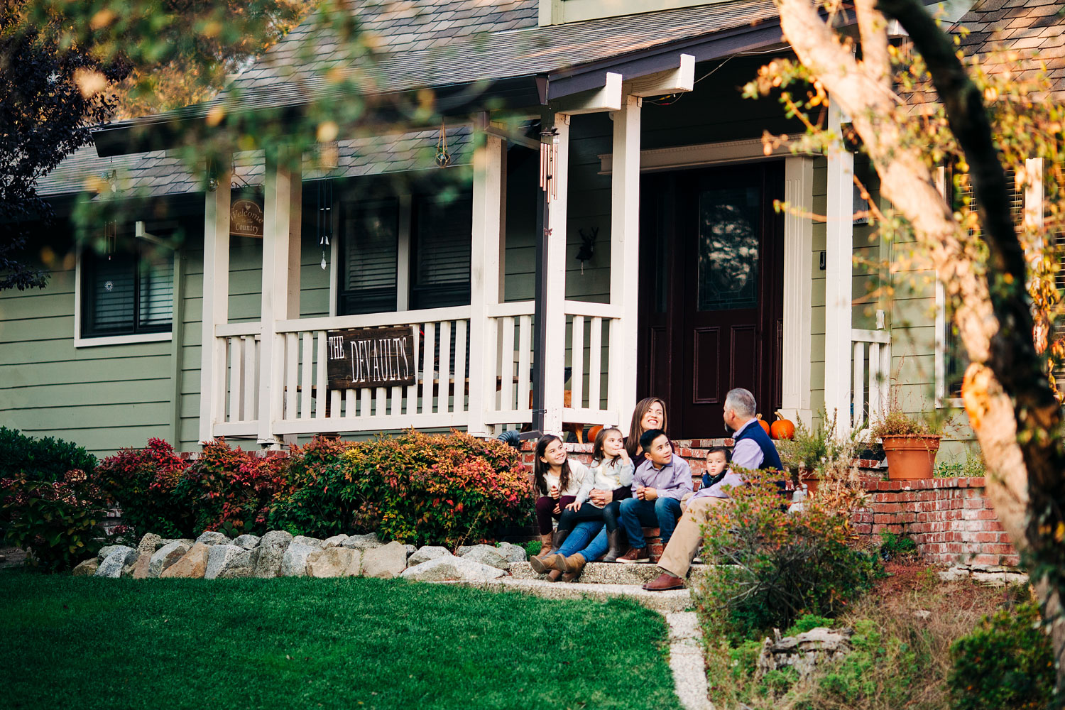 A family of six sits on their front porch during a lifestyle photo session with photographer Amy Wright in Rocklin, California.