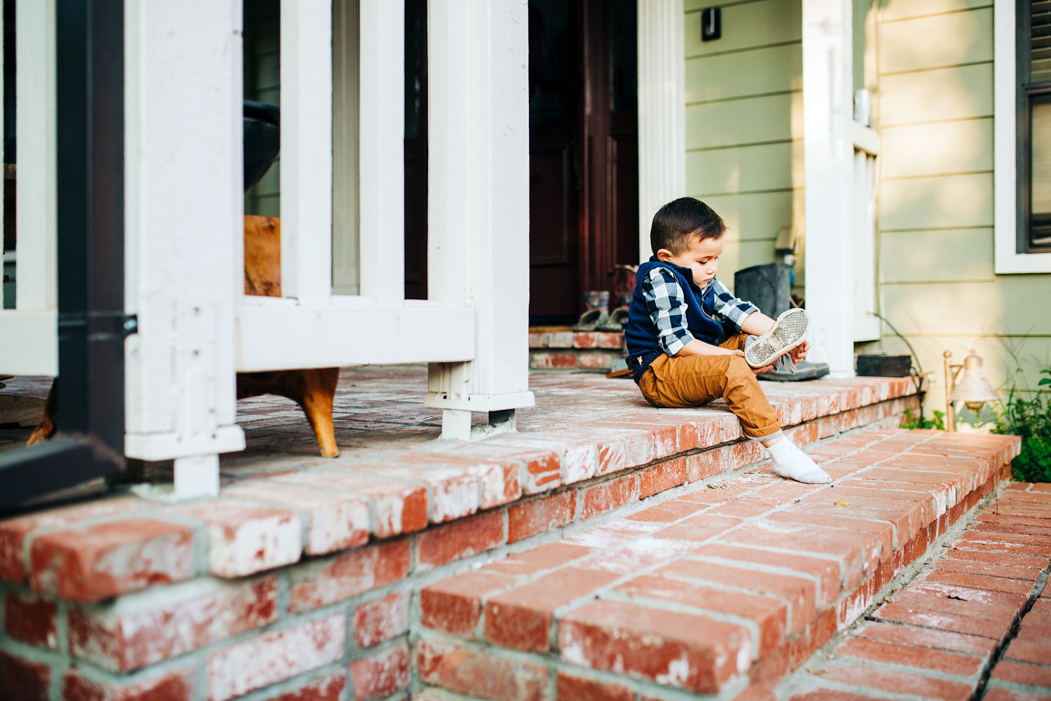 A boy puts on his shoes on the front porch steps during a lifestyle home photo session with Amy Wright Photography in Roseville, California.