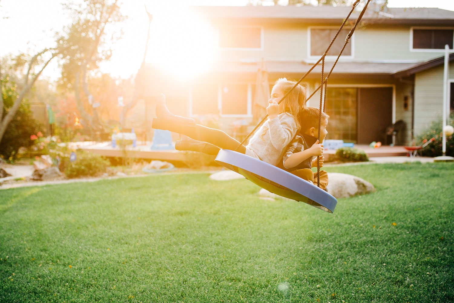 Two siblings swing in their light filled backyard during a home family photo session with Amy Wright Photography in Roseville, California.