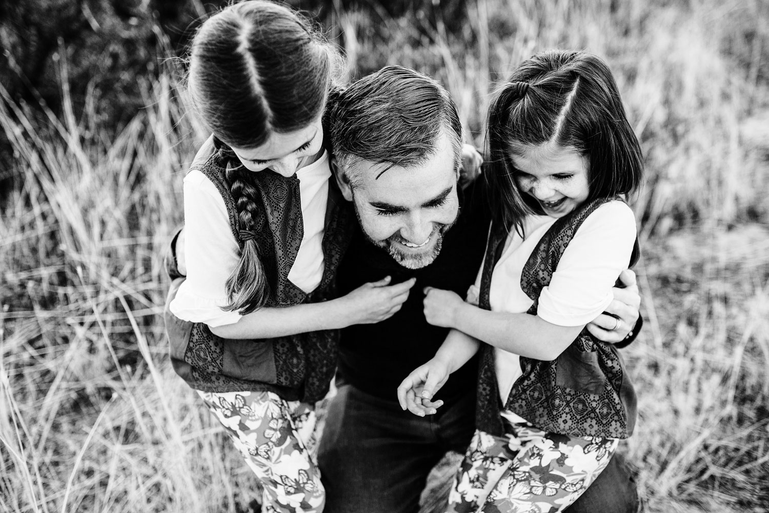 A dad lovingly plays with his two daughters during a fun family photo session with Amy Wright in Sacramento, California.