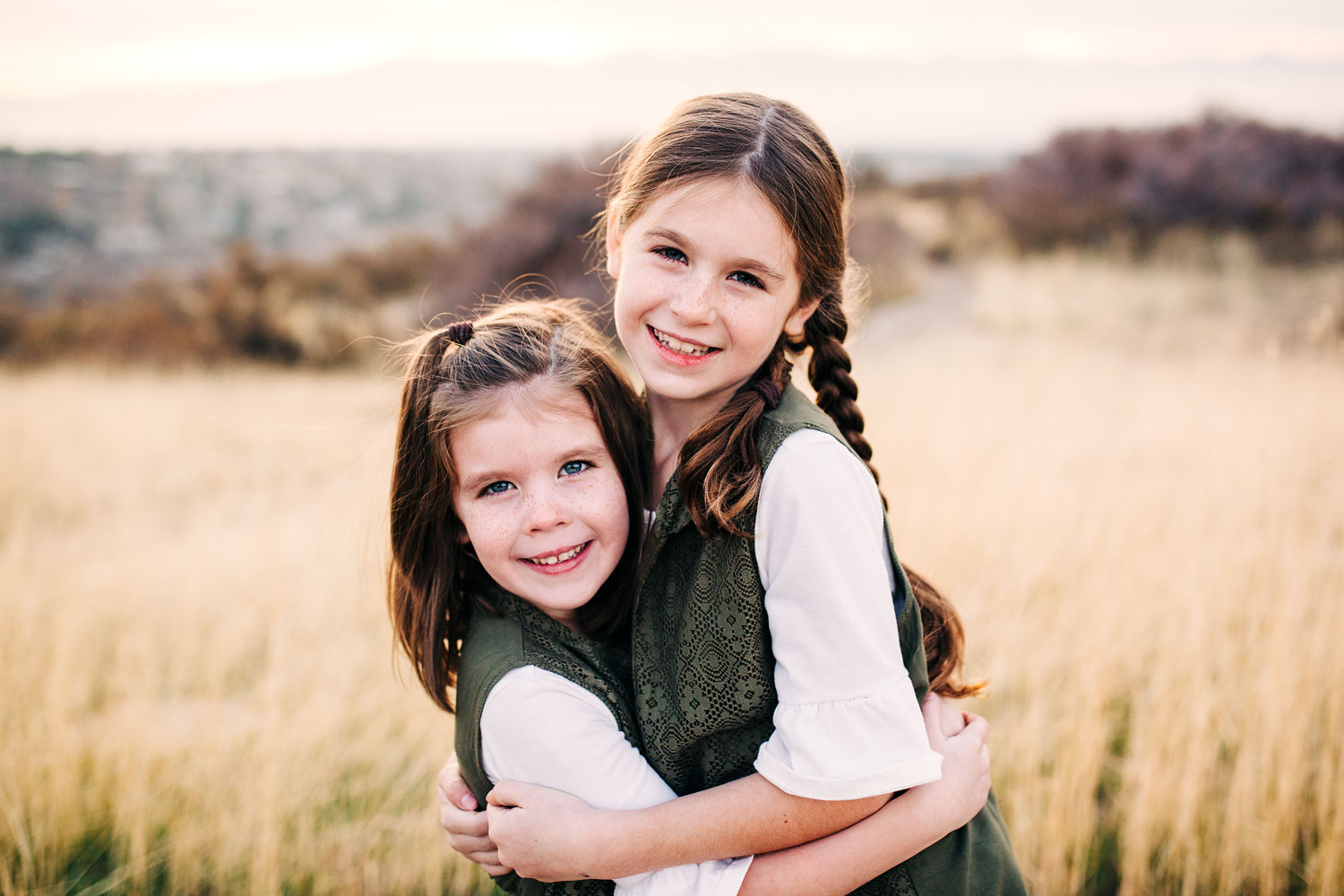 Two sisters lovingly wrap their arms around each other during a family photo shoot with Amy Wright Photography, in Roseville, California.
