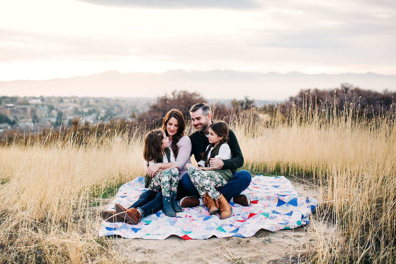 A family of four sits on a quilt at the top of a hill during their lifestyle family photo shoot with Amy Wright, a photographer based out of Roseville, California.